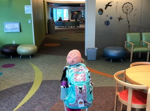 Photo of Nora with her bag walking into the hospital
